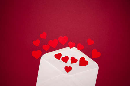 Envelope with hearts on red background. Romance and love concept