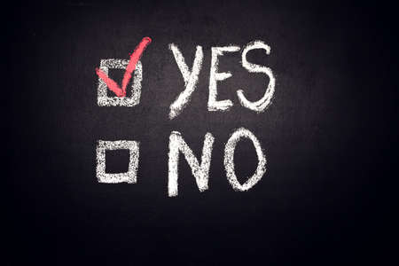 Two checkboxes with words Yes and No with check mark near Yes on blackboard. Choice and test concept