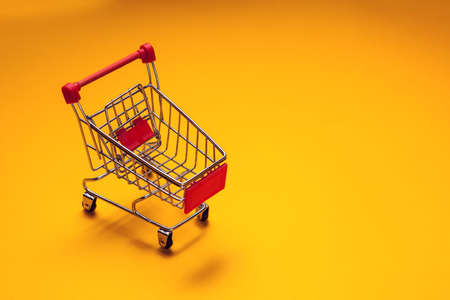 Empty trolley on yellow background. Shopping concept Stock fotó - 163816959