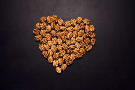 Unpeeld walnuts in the shape of heart in the middle of black background. Organic and healthy food