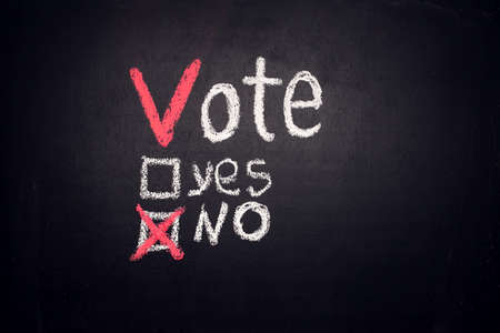 Vote checkboxes with words Yes and No with check mark near No on blackboard. Voiting concept