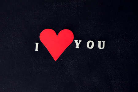 I Love You phrase with heart symbol on the black background. Romance and holiday concept