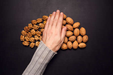 Walnuts peeld and unpeeld with hand in the middle of black background. Organic and healthy food Stock fotó