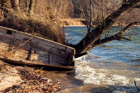 Old wooden fishing boat on the lake shore in late fall Stock fotó