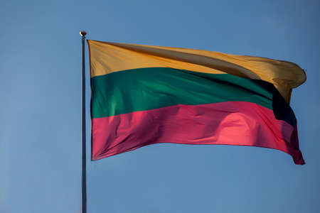 The flag of Lithuania flying against blue sky background