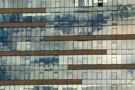 Glass building facade with reflection of clouds. Stock fotó