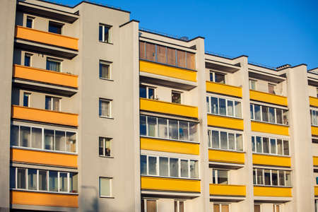 Exterior of apartment building on a blue sky background. No people. Real estate business concept.