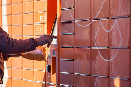 Man using automated self service post terminal machine or locker to deposit a parcel for storage