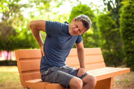 Man with back pain in the park. Healthcare and medicine concept Stock fotó