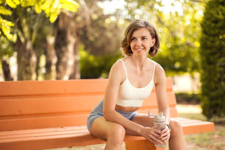 Sports woman drinking water in the park. Fitness and healthcare concept