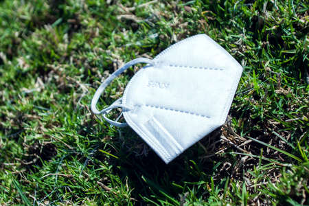Used face medical mask from  virus thrown away on field grass. World pandemic and environmental pollution concept