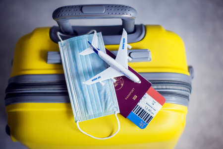 Traveling during  pandemic. Yellow luggage, medical mask, passport with ticket and toy plane.