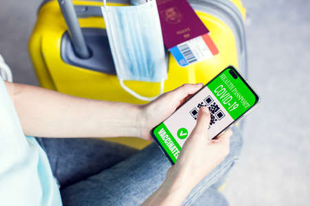 Health passport of vaccination in smartphone with qr-code, passport, tickets and luggage. Traveling during covid-19 pandemic. Stock fotó