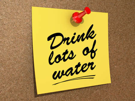 A note pinned to a cork board with the text Drink Lots of Water  Stock Photo