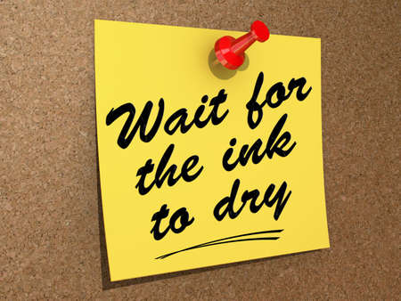 prudent: A note pinned to a cork board with the text Wait For the Ink to Dry. Stock Photo