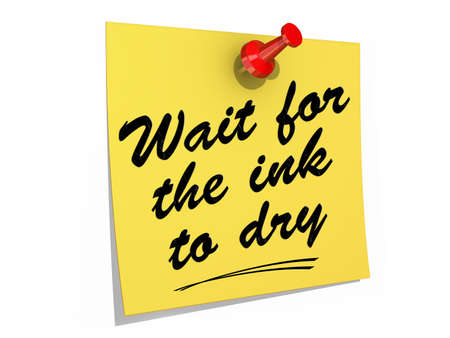 A note pinned to a white background with the text Wait For the Ink to Dry. Stock fotó