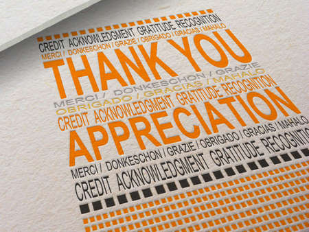 The word Thank You letterpressed into paper with associated words around it