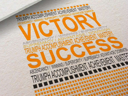 The word Victory letterpressed into paper with associated words around it.