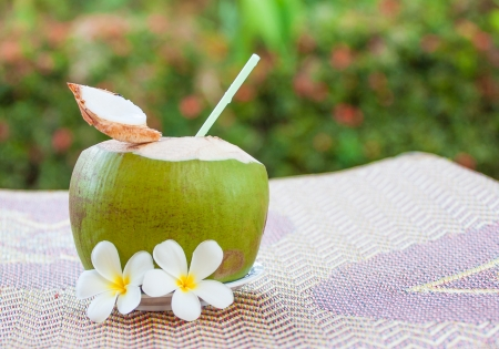 closed up sweet young coconut with drinking straw photo
