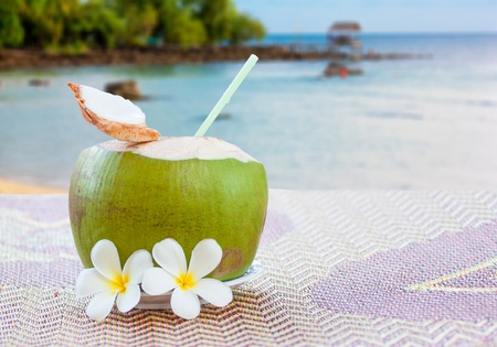 closed up sweet young coconut with drinking straw