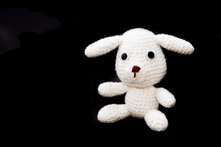 handmade crochet white yarn doll on black background