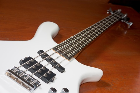 white electric guitar bass lay down on a wood table photo