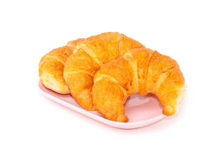 isolated croissant in pink plate