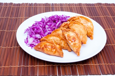 Deep fried gyoza and sliced purple cabbage in white plate on bamboo mat