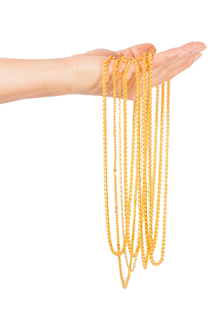 golden necklace in left hand isolated on white