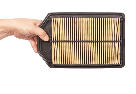 impure: hand holding an old and dirty of car air filter isolated on white
