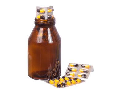 yellow and black capsules drug and bottle isolated on white Stock Photo