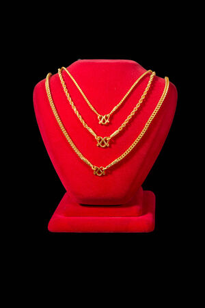 Realistic red stands for jewelry with golden necklace  isolated on black Standard-Bild
