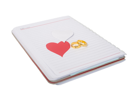 golden ring on notebook with heart isolated on white photo