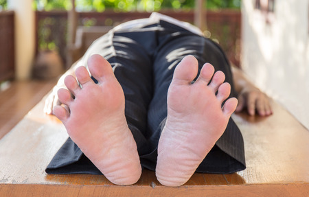 whacked: foot view of man lay down on the wood table