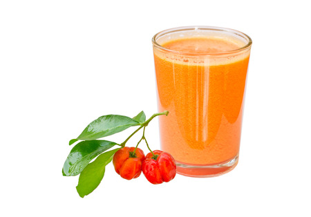 A glass of acerola juice extract and acerola fruit with leaf isolated on white
