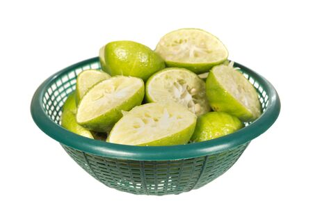 squeezed lemon in green basket isolated on white