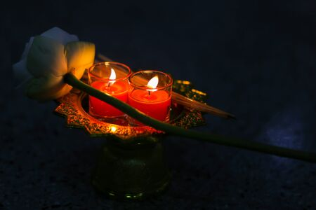 red candle with lotus and incense on golden tray