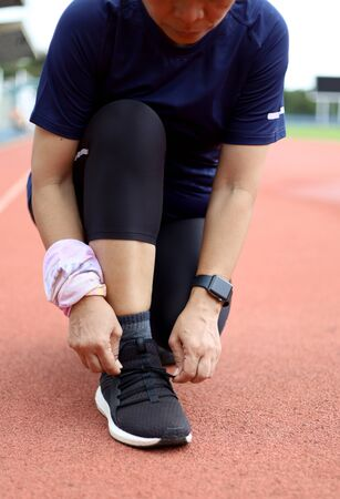 asia women tie her sport shoes on running track