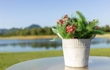 Pot with artificial flower on circle outdoors table with blur lake view