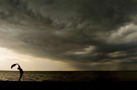 Silueta de una mujer de pie bajo la tormenta Foto de archivo - 43474542