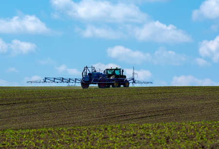 crop margin: Tractor with a trailed sprayer. Treatment of the field with young maize. Stock Photo