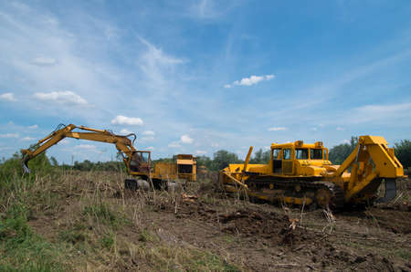 Digger and bulldozer clearing forest land.