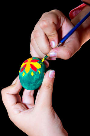 Child decorates Easter egg with brush and paint.