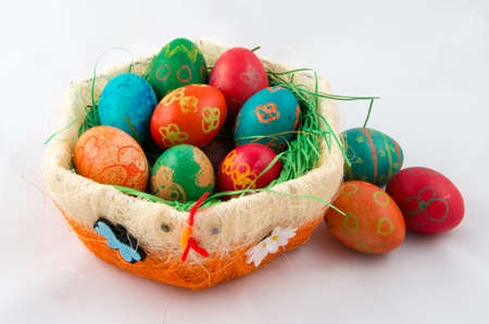 Decorative basket with Easter eggs on the bright background Stock Photo