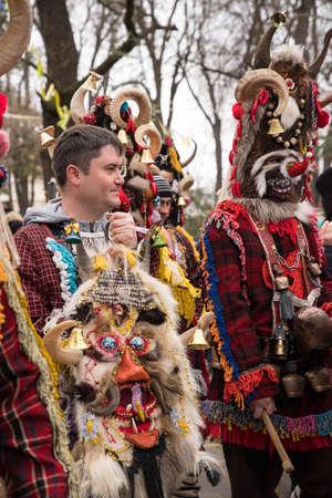 People in traditional carnival costumes at Kukeri festival kukerlandia Yambol, Bulgaria. Participants from Moldova
