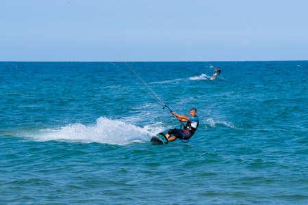 Shkorpilovtsi, Bulgaria - June 29, 2018: Kiteboarder athlete performing kiteboarding tricks on the water in the sea. Kiteboarding, Kitesurfing Sports. 에디토리얼
