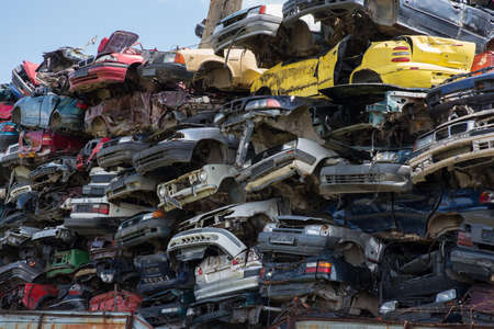 Stacked junk yard clunker cars prepared for recycled