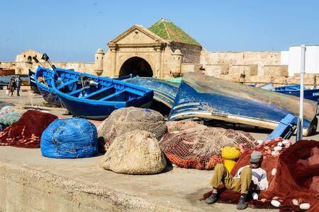 A fisherman sleeping on the harbor in Essaouira, Morocco