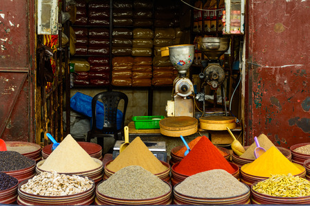 A vendor selling colorful spices on the street in Morocco