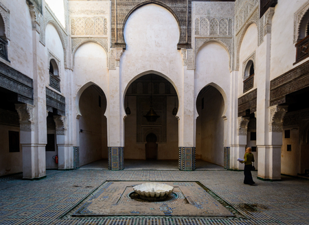 A woman inside an Inner Yard (Riad) with colorful tiles on the floor, Morocco